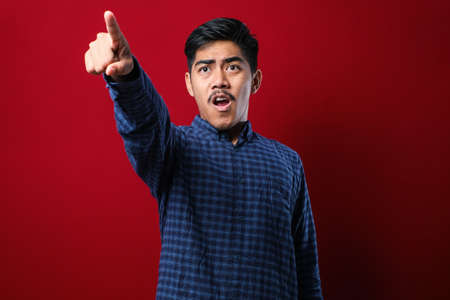 Young handsome asian man wearing casual shirt standing over red background pointing with finger surprised ahead, open mouth amazed expression, something on the front Stock Photo