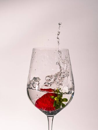 Image with white background of a glass with water a strawberry falls and freezes the movement of the water with splashing out of the glass
