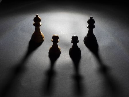 Image of two bishops a black and a white and two pawns a black and a white backlighting with black background Foto de archivo