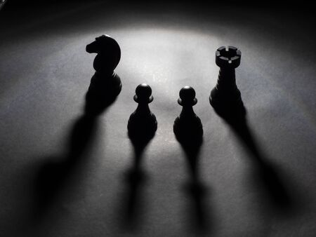 Image of black knight and rook and two black pawns backlighting with black background Foto de archivo