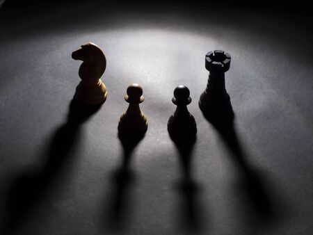 Image of white knight and black rook and a black pawn and a white pawn backlighting with black background Foto de archivo