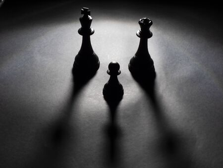 Image of black king and queen chess and a black pawn backlighting with black background