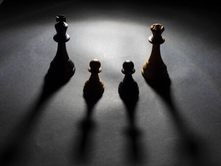Image of black king and white queen chess and a black pawn and a white pawn backlighting with black background Foto de archivo