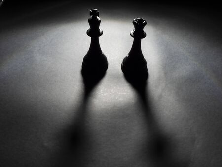 Image of black king and queen chess backlighting with black background