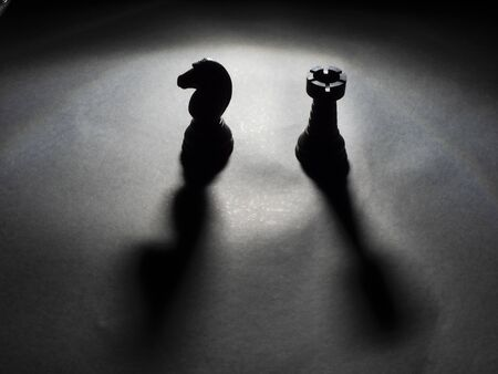 Image of black knight and rook backlighting with black background