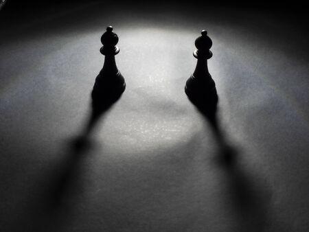 Image of two black bishops backlighting on black background Foto de archivo