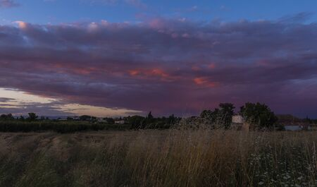 Red colored clouds and yellow vegetation