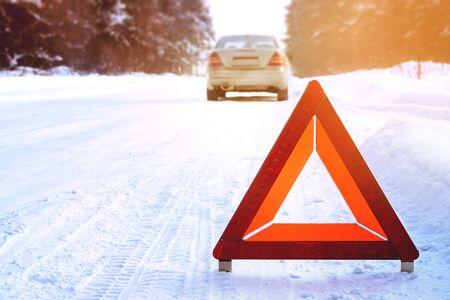 Segnale di arresto di emergenza rosso rotto argento auto inverno strada foresta sole