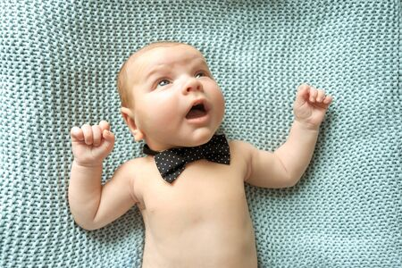 Cheerful white baby dressed in a bow tie lying on a knitted surface Stock Photo