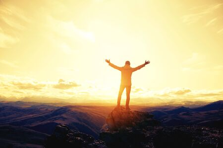 Traveler or hiker stands with raised arms against mountains
