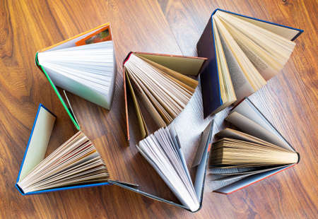 Books stack on wooden table, top view flat lay. Reading, learning, literature concept Imagens