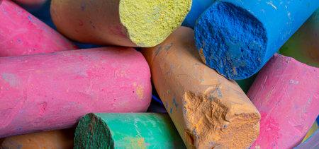 Colored chalks arranged diagonally over a white Archivio Fotografico