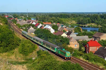 Passenger train passes the village with the river in background photo