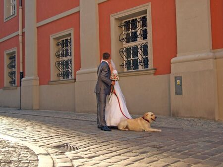 Bride and groom standing with a dog at old town photo