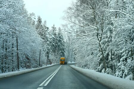 Yellow truck passing the snowy forest