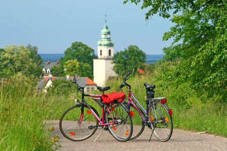 Two bikes standing on the road with a church in background - break during bicycle trip Stock Photo