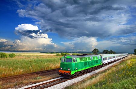 Intercity train passing the countryside with colorful sky over Stock Photo