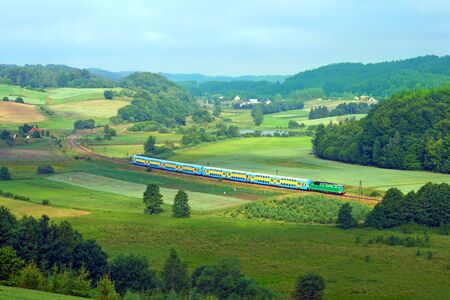 Landscape with a railway line, train, lake and forests Stock Photo