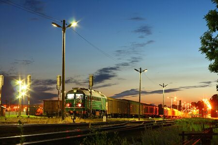 Freight train waiting at station during the evening Stock Photo