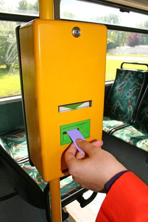 Woman is validating the ticket in the bus ticket validator