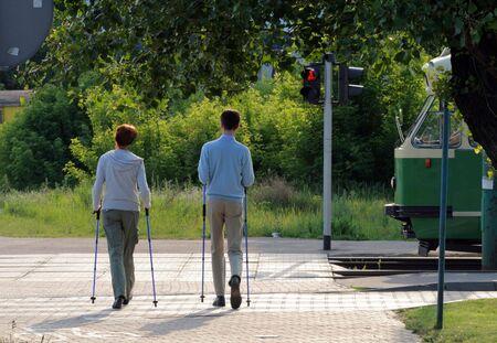 Happy couple doing nordic walk through the city photo