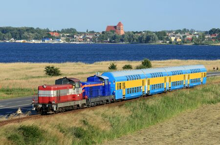 Double deck train hauled by the two diesel locomotives against baltic sea and coastal line photo