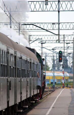 Steam retro train starting from the platform at railway station photo