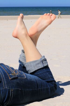 Woman in jeans with crossed legs resting on the beach photo
