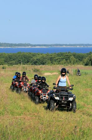 Group of young children riding quad / four-wheelers 4x4 on the meadow at the coastline