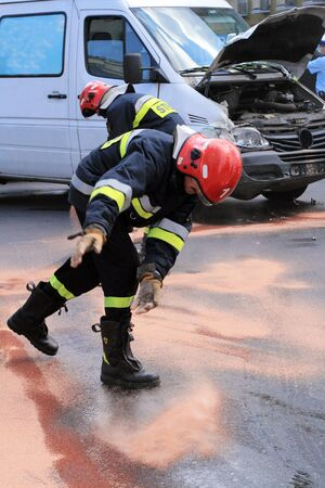 Fire fighters throwing the sand on the street with oil from smashed car