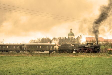 telegraphy: Old retro steam train passing the fields with a palace in background