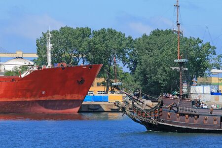 Cargo ship and pirate touristic ship passing together on the port channel photo