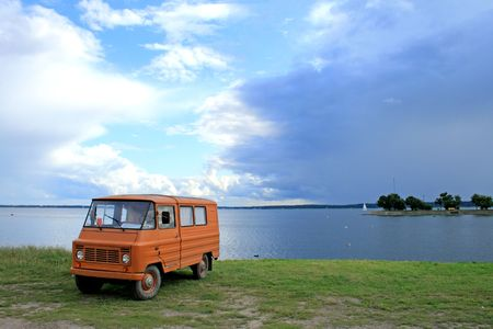 Vintage van as a camper standing on shore of the lake