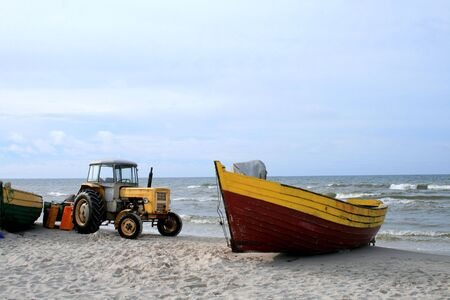 Yellow tractor and wooden boat on the beach photo