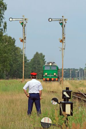 Railway traffic controller giving a signals to the train crew Imagens - 5585148