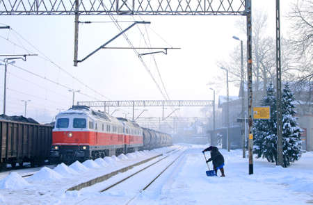 diesel locomotives: Freight train with diesel locomotives and woman shoveling the snow at the railway station