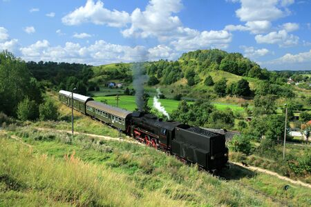 Beautiful hilly landscape with an old retro steam train photo