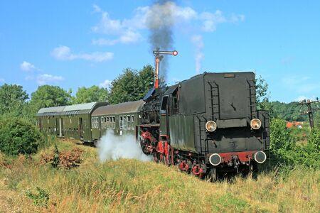 Old retro steam train passing through polish countryside Stock Photo