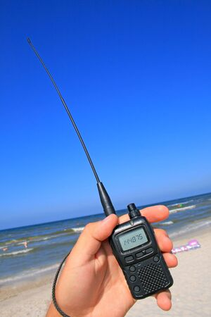 VHF transceiver in a hand against the beach and blue sky