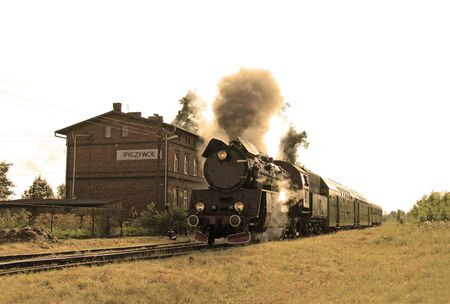 Old retro steam train starting from the small station Stock Photo