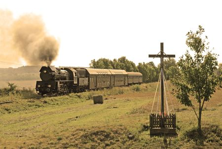 wood railroads: Old retro steam train passing through polish countryside Stock Photo