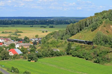 Beautiful hilly landscape with an old retro steam train Stock Photo