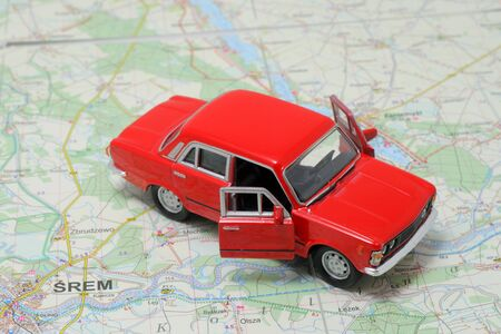 Tiny red car model on the road map photo