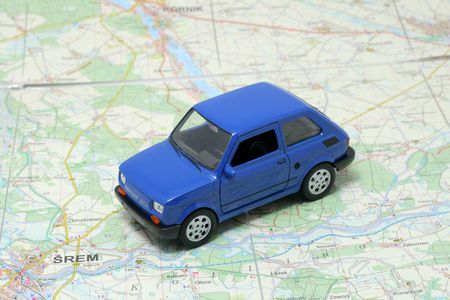 Tiny blue car model on the road map