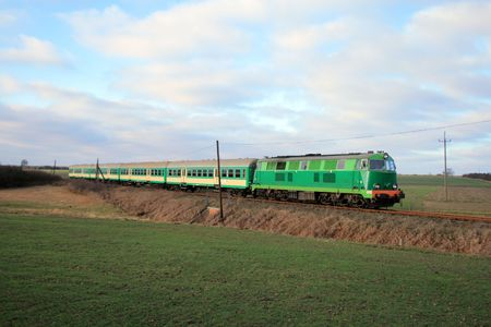 Rural landscape with train hauled by the diesel locomotive Stock Photo