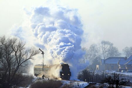 Vintage steam train starting from the station during wintertime Stock Photo