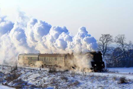 Vintage steam train passing through snowy countryside photo