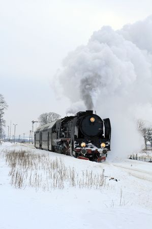 Old retro steam train starting from the station during wintertime Stock Photo