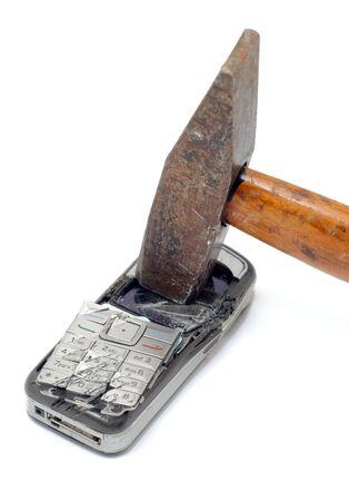 Hammer smashing cellular phone isolated on the white background