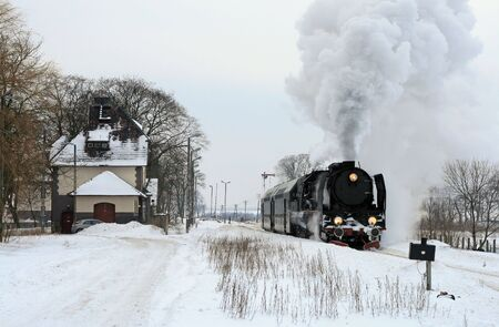 railroad transportations: Old retro steam train starting from the station during wintertime Stock Photo